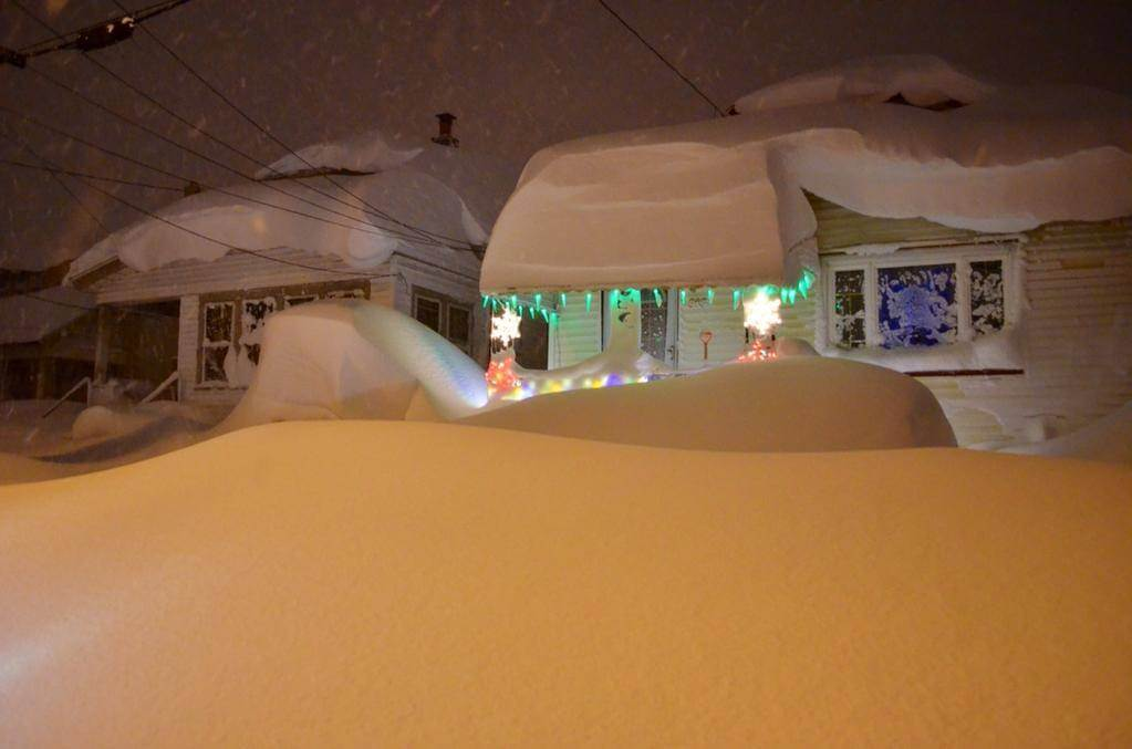 A car is buried in this snow, but you wouldn't know it. Roof collapses are a real possibility during this event.